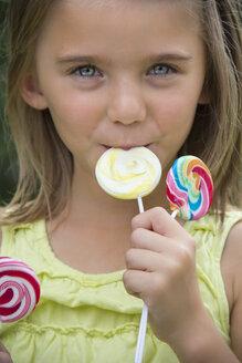 Portrait of girl holding lollipops - YFF000214