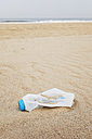 Belgium, empty plastic bottle lying on sandy beach at North Sea coast - GWF003127