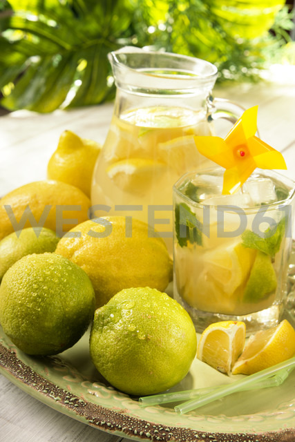 Carafe of home made lemonade splash and a drinking glass with slices of lemon - CSTF000369
