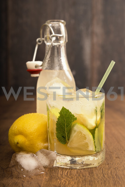 Glass of home made lemonade splash with slices of lemon and clip-top bottle - CSTF000371 - Carmen Steiner/Westend61