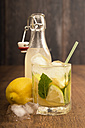 Glass of home made lemonade splash with slices of lemon and clip-top bottle - CSTF000371