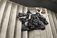 Woman wearing dress made from bin bags lying on stairs - FCF000416