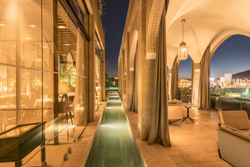 Morocco, Fes, view to lighted water basin and roofed terrace of a hotel by night - KM001371