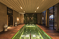 Morocco, Fes, view to lighted indoor pool  of a hotel at twilight - KM001384