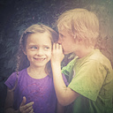 Germany, Landshut, Boy whispering into girl's ear - SARF000755