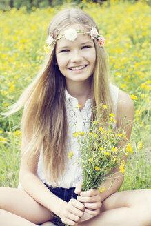 Portrait of a happy girl sitting on a flower meadow wearing flowers - GDF000387