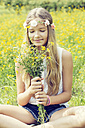 Portrait of a girl sitting on a flower meadow smelling on a bunch of flowers - GDF000368