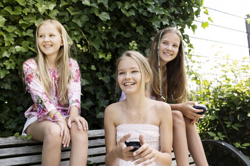 Three smiling girls sitting on a park bench - GDF000369