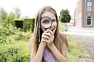 Girl looking through magnifying glass - GDF000384