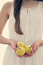 Young woman holding three pears in her hands, partial view - BRF000569