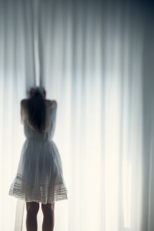 Young woman hiding her face behind a white curtain, back view - BRF000575