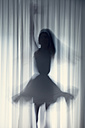 Silhouette of a young woman dancing in front of a white curtain - BRF000570