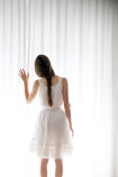 Young woman touching a white curtain, back view - BRF000572