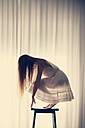 Young woman crouching on a stool in front of a white curtain, back view - BRF000581