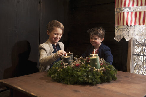 Two little boys lightning candles on a Advent wreath - HHF004846