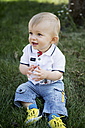 Germany, Oberhausen, Blond baby boy sitting on grass in park - GDF000397