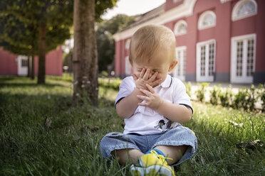 Germany, Oberhausen, Blond baby boy sitting in park of Oberhausen Castle - GDF000403