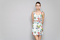 Young woman wearing patternd summer dress leaning against grey wall - TCF004092