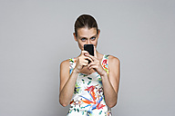 Young woman photographing with smartphone - TCF004107