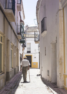 Spain, Andalusia, Tarifa, Old town, one senior man walking in an alley - KB000125