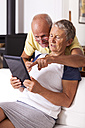 Senior couple at home using digital tablet - JUNF000005