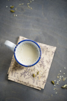 Cup of soy rice milk with cardamom and cinnamon on napkin aund wood, elevated view - MYF000527