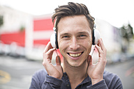 Portrait of smiling young man listening music with headphones - ZEF000032