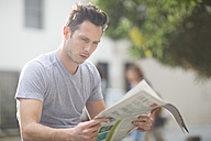 Portrait of young man reading newspaper - ZEF000073