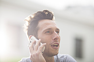 Portrait of young man telephoning with smartphone - ZEF000075
