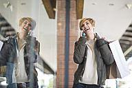 Portrait of laughing woman telephoning in front of a window display - ZEF000150