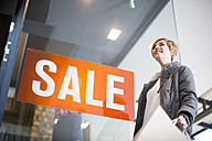 Woman standing in front of a window display with sign Sale - ZEF000093
