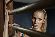 Serious woman at wallbars in gym - MFF001160