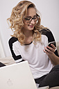 Portrait of young woman using smartphone and laptop at home - JUNF000022