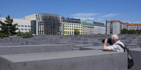 Germany, Berlin, Holocaust Memorial, Senior man photographing steles - WIF000950