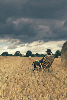 Teenage boy with hat sitting in a rocking chair on a grainfield - MS004160