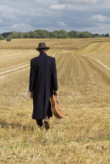Teenage boy with hat and long coat walking on a grainfield with guitar - MS004165