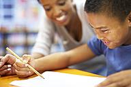 Young woman teaching boy writing on paper - ZEF000755