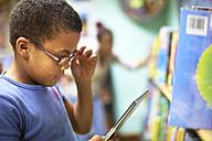 Boy in library holding digital tablet - ZEF000757