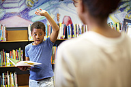 Boy in library raising his hand - ZEF000184