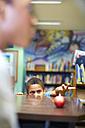 Boy in library peeking at apple - ZEF000187