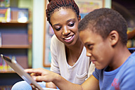 Young woman and boy with digital tablet in library - ZEF000189