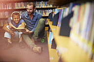 Man reading book to boy with headphones in library - ZEF000761