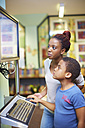 Young woman and boy using computer in library - ZEF000205