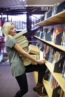 Female student carrying pile of books in a library - ZEF000133