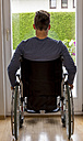 Man in wheelchair looking out of window - EJWF000588