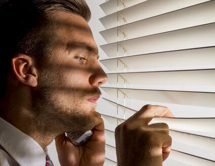 Man peeking through sunblind - EJWF000590