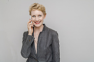Portrait of smiling blond woman telephoning with smartphone in front of grey background - TCF004234