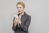 Portrait of distraught blond woman looking at her smartphone in front of grey background - TCF004235