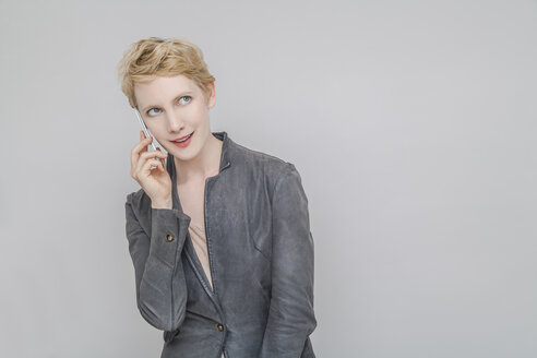 Portrait of smiling blond woman telephoning with smartphone in front of grey background - TCF004238