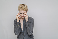 Portrait of pensive blond woman telephoning with smartphone in front of grey background - TCF004239